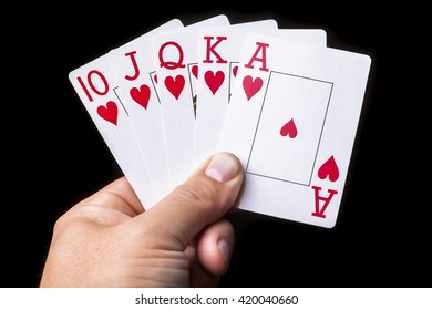 Hand holding 5 playing cards with a Royal Flush.  Black background.