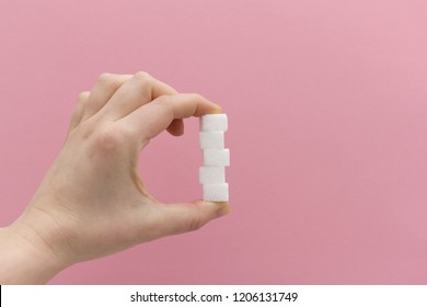 Hand holding 5 sugar cubes between fingers