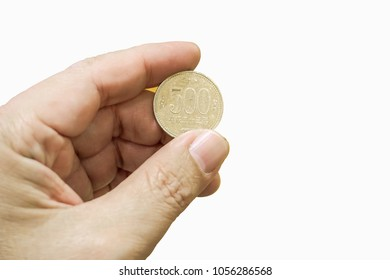 Hand holding 500 Yen Japanese coin isolate on white background.
