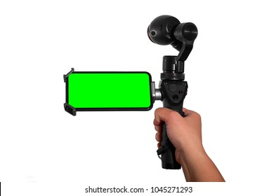 A hand holding an action 4k video camera and mobile phone with chroma key on it. With Excellent Clipping Path. Video concept.
