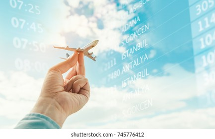 hand holding airplane model in front of cloudy blue sky background and departure board
