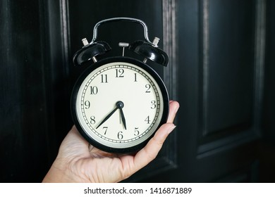 Hand holding an alarm clock, wake up or time concept