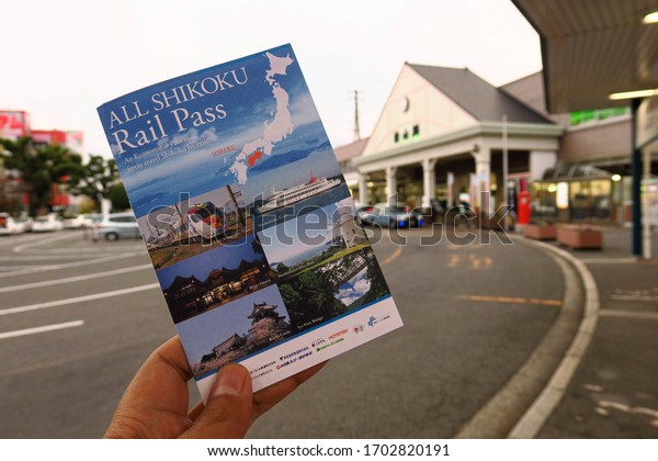 Hand holding All Shikoku rail pass in  front of Matsuyama Train Station in  Ehime City, Japan