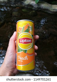 Hand holding aluminium can of Lipton ice tea with peach on river background, July, 2018, Chiang mai, Thailand
