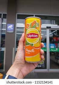 Hand holding aluminium can of Lipton ice tea with peach on 7-11 shop background, July, 2018, Chiang mai, Thailand