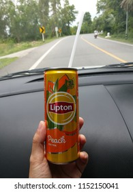 Hand holding aluminium can of Lipton ice tea with peach on road background, July, 2018, Chiang mai, Thailand