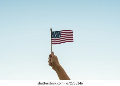 Hand holding American flag in air against sky