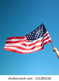 Hand holding american flag on the blue sky background