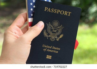Hand holding American flag and passport