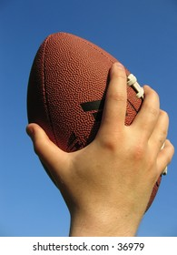 A hand holding an American football against the blue sky.