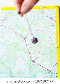 Hand holding a amethyst crystal pendulum above the map. Alternative way of searching missing people concept.