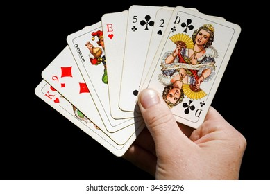 hand holding anglo-american playing cards isolated on black