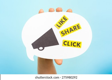 """Hand holding a announce with megaphone and the words """"LIKE"""" """"SHARE"""" """"CLICK"""", on blue background. Social media and internet concept. Native advertising concept. Influencer marketing."""