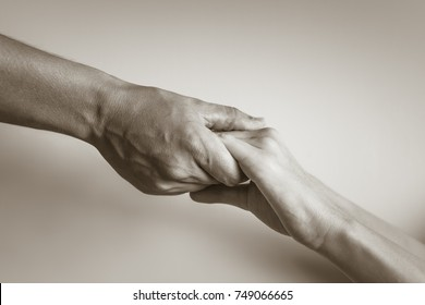 Hand holding another, comfort helping.