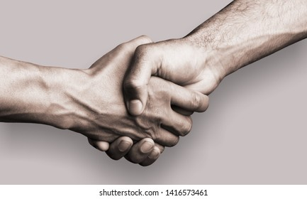 Hand holding another hand on gray background