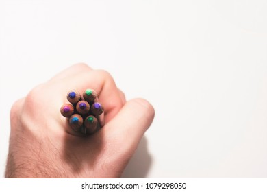 A hand holding an arrangement of cool colored pencils on an isolated paper white background.