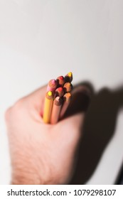 A hand holding an arrangement of warm colored pencils on an isolated paper white background.