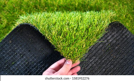 Hand holding an artificial grass roll. Greenering with an artificial turf.