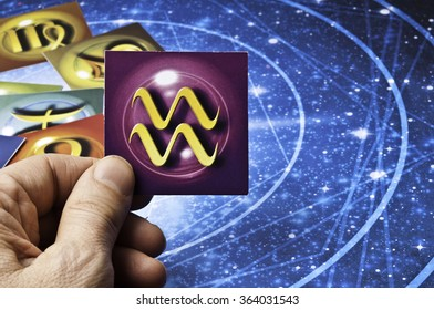 hand holding an astrology card with symbol of sign of Aquarius