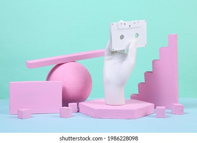 Hand holding Audio cassette with pink geometric shapas on blue background. Concept art. Minimalism