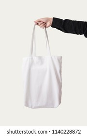 Hand holding bag canvas fabric for mockup blank template isolated on white background.