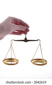 A hand holding a balance scale.