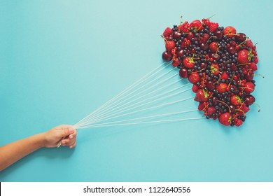 Hand holding balloons made of berries on blue paper background. Healthy eating concept. Flat lay. Toned