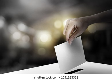 Hand holding ballot paper for election vote concept at colorful background. corrupt election vote concept.