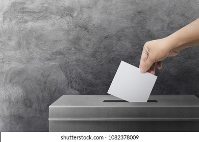 Hand holding ballot paper for election vote concept background.