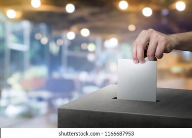 Hand, die Wahlurnen für das Konzept der Wahl auf Zimmer-Hintergrund.