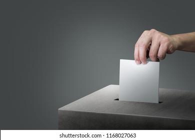 Hand, die Wahlurne auf schwarzem Hintergrund hält.