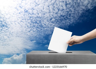 Hand holding ballot paper for election vote at blue sky background, freedom of election vote concept.