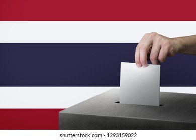 Hand holding ballot paper for election vote at thailand national flag on background. Thailand voting concept.