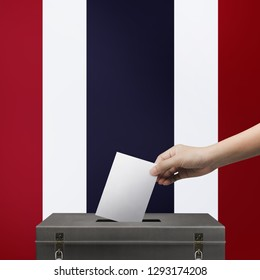 Hand holding ballot paper for election vote at thailand national flag background. Thailand voting concept.
