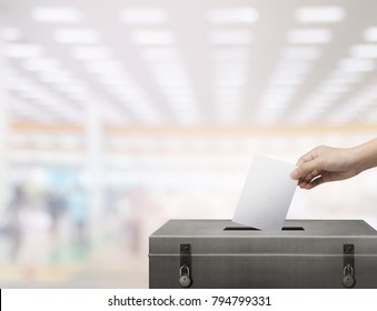 Hand holding ballot paper for election vote concept at hall background.