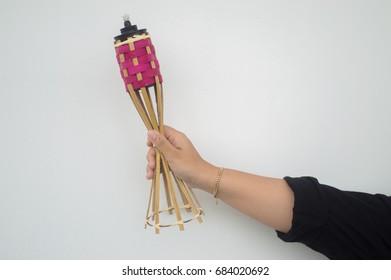 Hand holding a bamboo oil lamp for Hari Raya festival