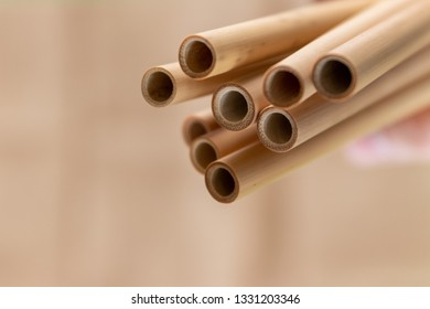 A hand holding bamboo straws on a natural-looking brown background