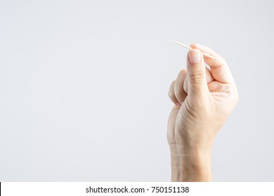 hand holding bamboo or wooden toothpick on white background
