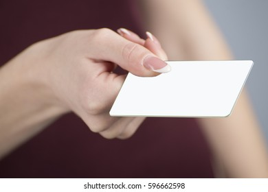 Hand holding a bank card on a light gray background.Close-up