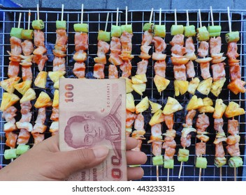 Hand holding banknote of Thailand with background barbecue many grilling on stove.