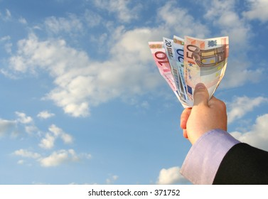 a hand holding up banknotes in front of a cloudy sky