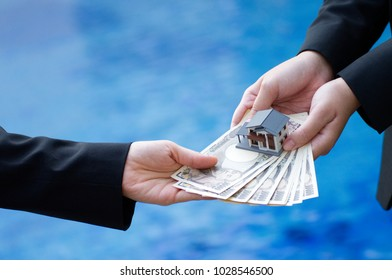 Hand holding banknotes of the Japanese yen and house model. Financial for real estate or money freedom concept.
