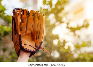 Hand holding Baseball glove on field with base and outfield .