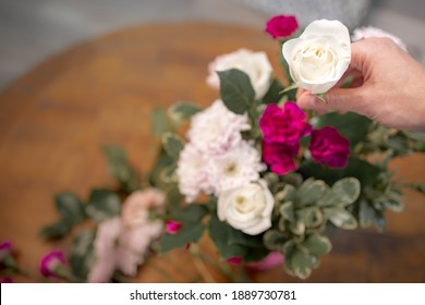 Hand holding beautiful blooming white rose over a bunch of colorful flowers and fresh green leaves at the wooden table, depth od filed. Florist arrangement flora at home for anniversary gift. Top view