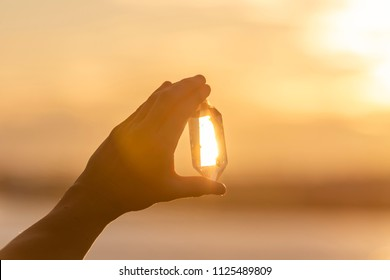 A hand holding up a beautiful quartz crystal outdoors in the sun