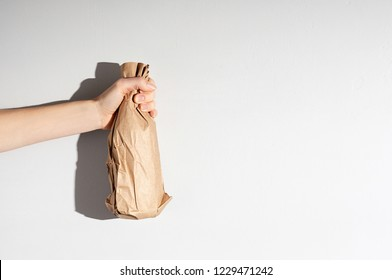 Hand holding beer bottle in the paper bag on gray concrete background. Close up view with copy space
