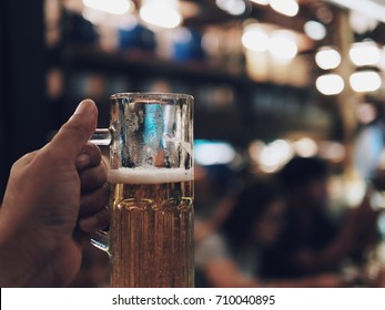 Hand holding Beer mug against the background of bar or restaurant. Free space for text. copy space.