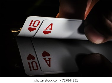 hand holding best classic winning blackjack combination ten and ace hearts