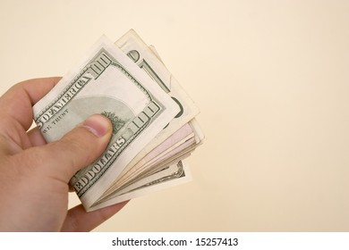 A hand holding a big wad of cash isolated over a gold background.