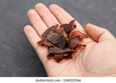 A hand holding biltong (cured meat). This is a traditional food snack in South Africa.